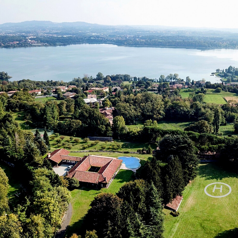 Aerial view of the lakefront property woth a simple helicopter pad in Eupilio, Lombardy, Italy